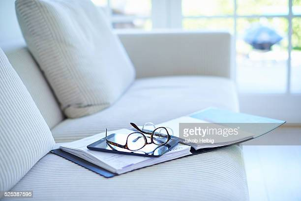 Eyeglasses and diary on living room sofa