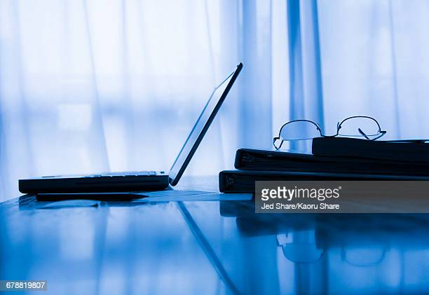 Eyeglasses and laptop near window curtains