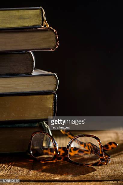 Eyeglasses and stack of books on table