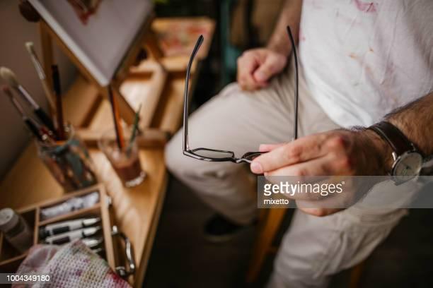 Eyeglasses in his hand