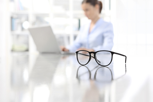 eyeglasses leaning on desk and woman working on computer at office in background 948721514