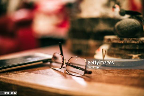 eyeglasses on table at home - reading glasses stock pictures, royalty-free photos & images
