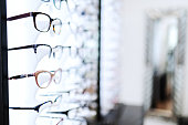 Eyeglasses sorted in line on shelf at optician.