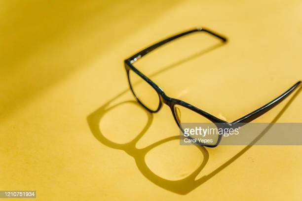 eyeglasses with shadow in yellow canvas - lunettes de lecture photos et images de collection