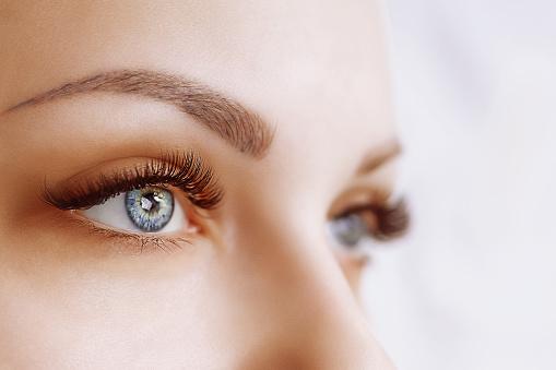 Eyelash Extension Procedure. Woman Eye with Long Eyelashes. Close up, selective focus 943394348