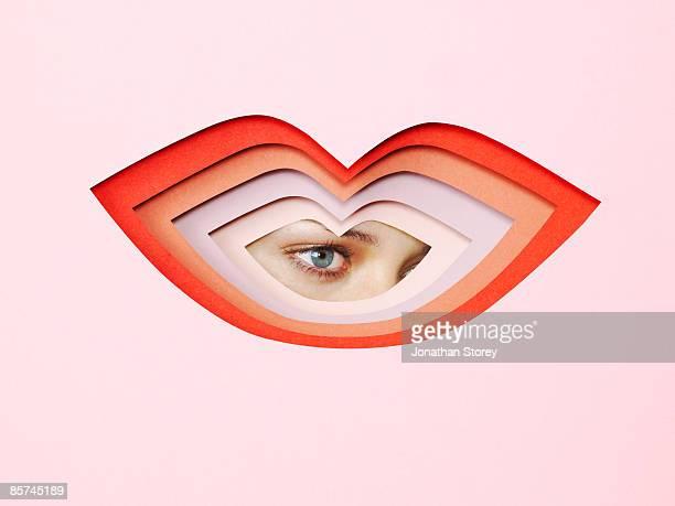 Eyes looking through cardboard cutout lips