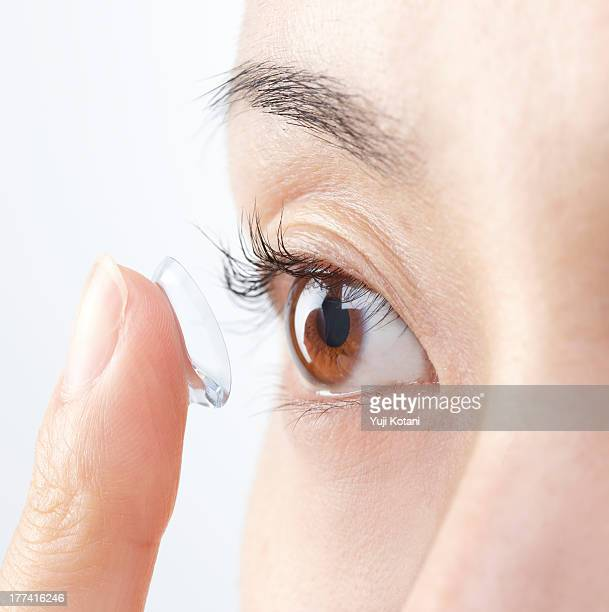 eyes of the woman who is going to attach a contact - contacts stock photos and pictures