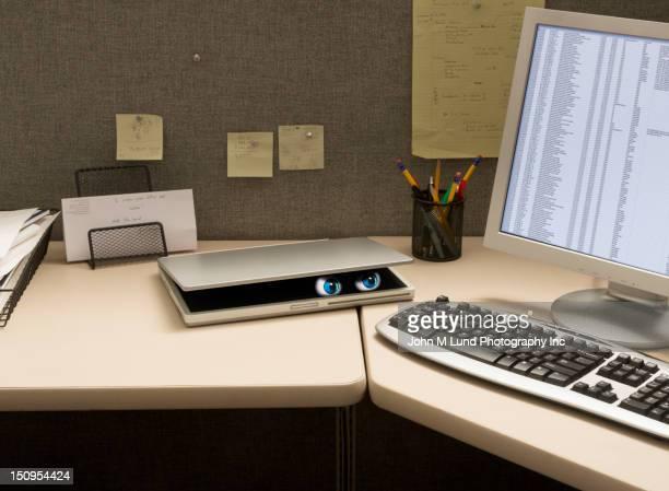 Eyes peering from laptop on desk