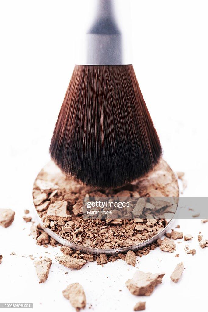 Eyeshadow brush above disc of eyeshadow powder, close-up : Stock Photo