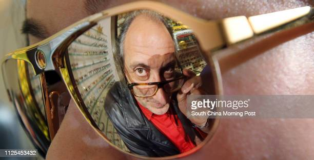 Eyewear designer Alain Mikli is reflected in a pair of sunglasses while posing for a photo in Central 12DEC12