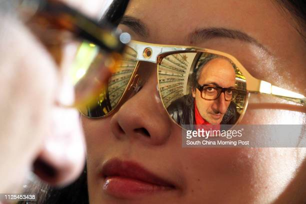 Eyewear designer Alain Mikli is reflected in a pair of sunglasses whilw posing for a photo in Central 12DEC12
