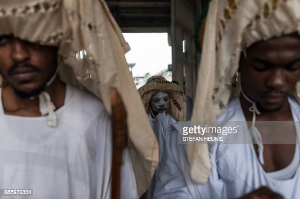 Eyo masqueraders look on as they arrive at the Tafawa Balewa Square in Lagos on May 20 2017 The whiteclad Eyo masquerades represent the spirits of...