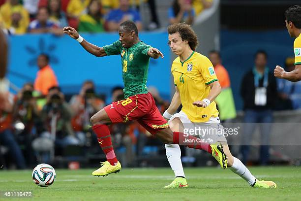 Eyong Enoh of Cameroon is tackled by David Luiz of Brazil during the 2014 FIFA World Cup Brazil Group A match between Cameroon and Brazil at Estadio...