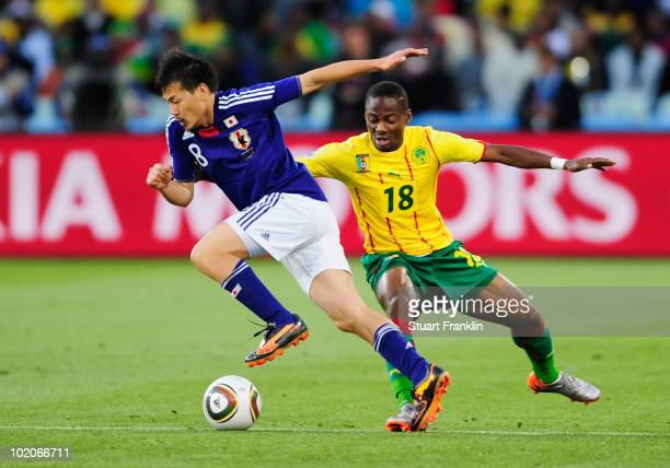 Eyong Enoh of Cameroon pressures Daisuke Matsui of Japan during the 2010 FIFA World Cup South Africa Group E match between Japan and Cameroon at the...