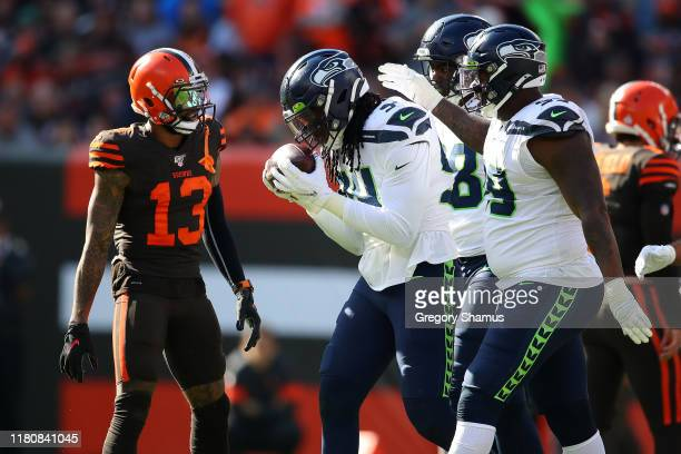 Ezekiel Ansah of the Seattle Seahawks celebrates his third quarter fumble recovery with teammates in front of Odell Beckham of the Cleveland Browns...