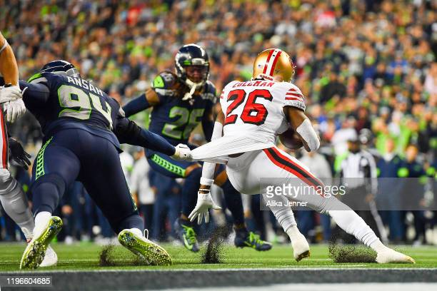 Ezekiel Ansah of the Seattle Seahawks, left, shirt tackles Tevin Coleman of the San Francisco 49ers during the second quarter of the game at...