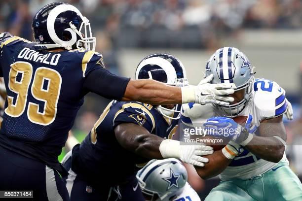 Ezekiel Elliott of the Dallas Cowboys carries the ball against Lamarcus Joyner of the Los Angeles Rams and Aaron Donald of the Los Angeles Rams in...