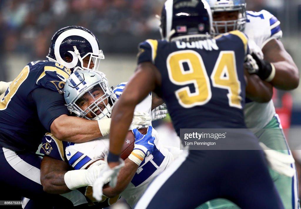Ezekiel Elliott #21 of the Dallas Cowboys carries the ball against Lamarcus Joyner #20 of the Los Angeles Rams, Robert Quinn #94 of the Los Angeles Rams and Aaron Donald #99 of the Los Angeles Rams in the second half at AT&T Stadium on October 1, 2017 in Arlington, Texas.