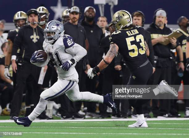 Ezekiel Elliott of the Dallas Cowboys carries the ball as he is pursued by AJ Klein of the New Orleans Saints in the first quarter at ATT Stadium on...