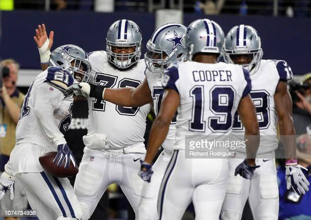 Ezekiel Elliott of the Dallas Cowboys celebrates a first quarter touchdown with Joe Looney La'el Collins and Amari Cooper at ATT Stadium on November...