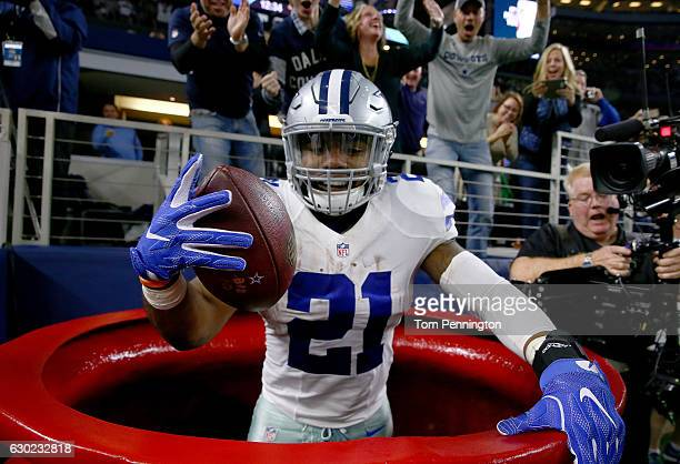 Ezekiel Elliott of the Dallas Cowboys celebrates after scoring a touchdown by jumping into a Salvation Army red kettle during the second quarter...