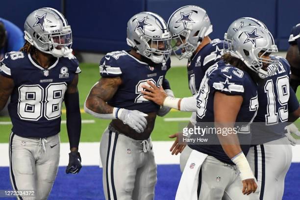 Ezekiel Elliott of the Dallas Cowboys celebrates with Dak Prescott after scoring a 19-yard receiving touchdown during the second quarter against the...