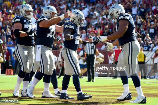 Ezekiel Elliott of the Dallas Cowboys celebrates with teammates after scoring a touchdown against the Washington Redskins during the second half at...