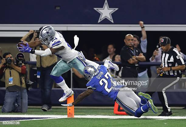 Ezekiel Elliott of the Dallas Cowboys dives across the goal line to score a touchdown as Glover Quin of the Detroit Lions defends during the first...