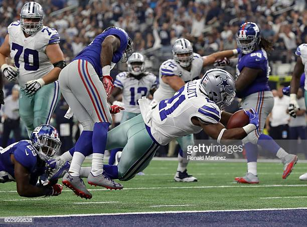 Ezekiel Elliott of the Dallas Cowboys dives to the end zone to score his first touchdown during the third quarter against the New York Giants at ATT...