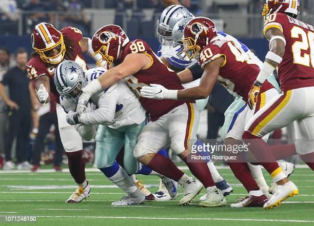 Ezekiel Elliott of the Dallas Cowboys fights for yards against Mason Foster Matthew Ioannidis and Josh HarveyClemons of the Washington Redskins at...