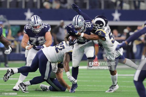 Ezekiel Elliott of the Dallas Cowboys gets hit by Tanzel Smart and Dante Fowler of the Los Angeles Rams at ATT Stadium on December 15 2019 in...