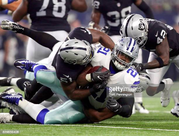 Ezekiel Elliott of the Dallas Cowboys gets tackled by Bruce Irvin Jelani Jenkins and Karl Joseph of the Oakland Raiders in the first quarter of a...
