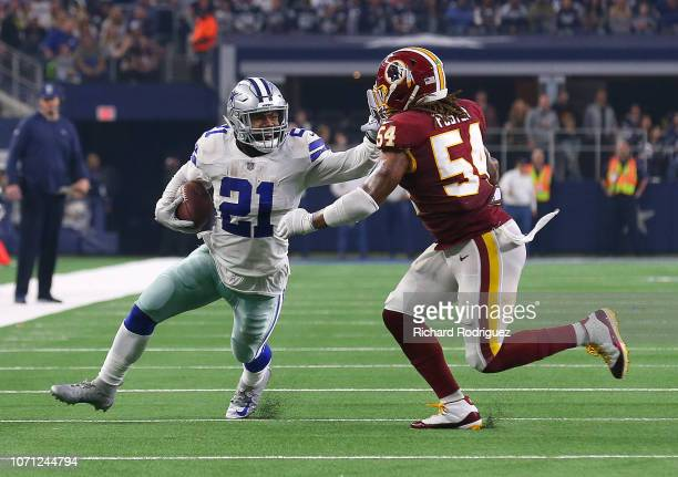 Ezekiel Elliott of the Dallas Cowboys holds off Mason Foster of the Washington Redskins on a run in the fourth quarter at ATT Stadium on November 22...