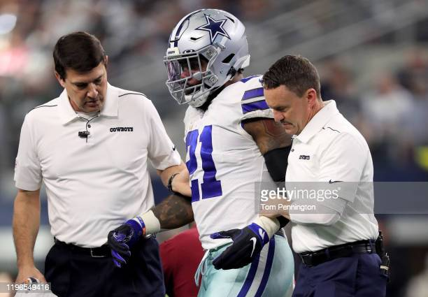 Ezekiel Elliott of the Dallas Cowboys is helped off the field after being injured in the first quarter against the Washington Redskins in the game at...