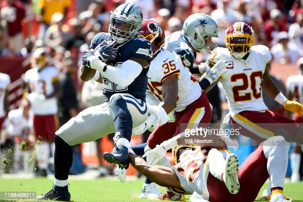 Ezekiel Elliott of the Dallas Cowboys is tackled by Jon Bostic and Montae Nicholson of the Washington Redskins during the first half at FedExField on...