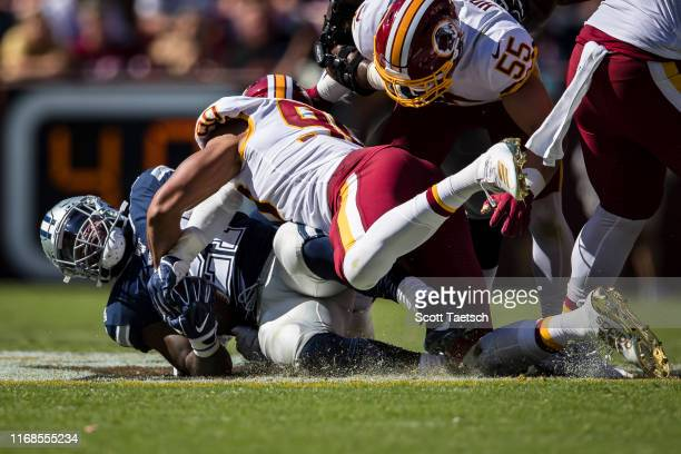 Ezekiel Elliott of the Dallas Cowboys is tackled by Montez Sweat of the Washington Redskins during the second half at FedExField on September 15 2019...