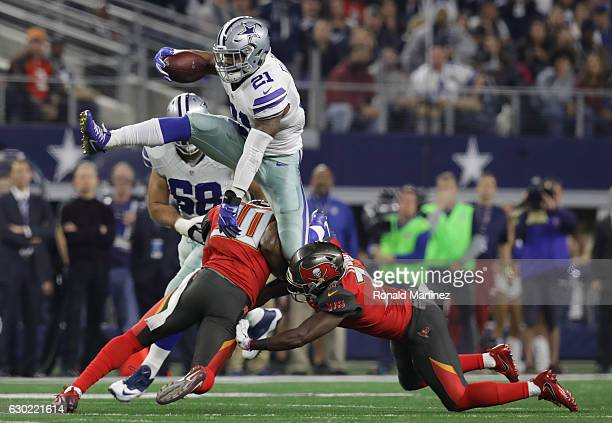 Ezekiel Elliott of the Dallas Cowboys jumps over the attempted tackle by Bradley McDougald and Keith Tandy of the Tampa Bay Buccaneers in the first...