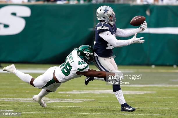 Ezekiel Elliott of the Dallas Cowboys makes a catch against the Neville Hewitt of the New York Jets during the first quarter at MetLife Stadium on...