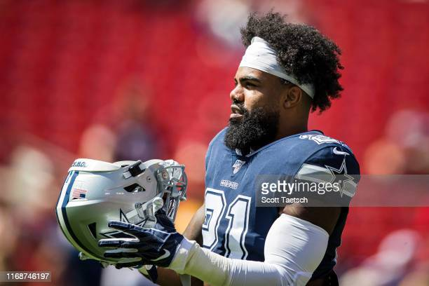 Ezekiel Elliott of the Dallas Cowboys puts his helmet on before the game against the Washington Redskins at FedExField on September 15 2019 in...
