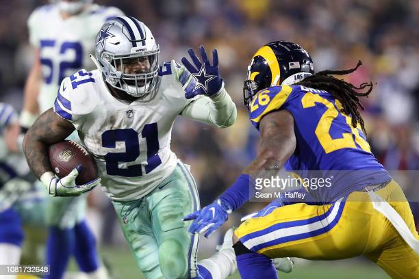 Ezekiel Elliott of the Dallas Cowboys runs with the ball against Mark Barron of the Los Angeles Rams in the fourth quarter in the NFC Divisional...