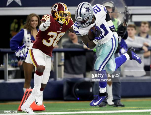 Ezekiel Elliott of the Dallas Cowboys runs with the ball while being tackled by Kayvon Webster of the Washington Redskins in the first quarter in the...