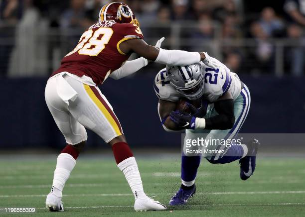 Ezekiel Elliott of the Dallas Cowboys runs with the ball while being tackled by Kayvon Webster of the Washington Redskins in the second quarter in...