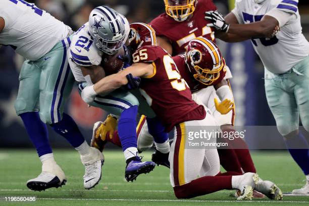 Ezekiel Elliott of the Dallas Cowboys runs with the ball while being tackled by Cole Holcomb of the Washington Redskins in the second quarter in the...