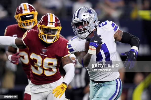 Ezekiel Elliott of the Dallas Cowboys runs with the ball while being tackled by Jeremy Reaves of the Washington Redskins in the second quarter in the...