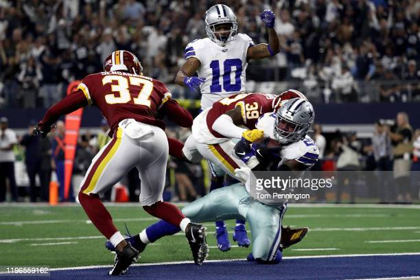 Ezekiel Elliott of the Dallas Cowboys scores a touchdown past Coty Sensabaugh and Jeremy Reaves of the Washington Redskins in the second quarter in...