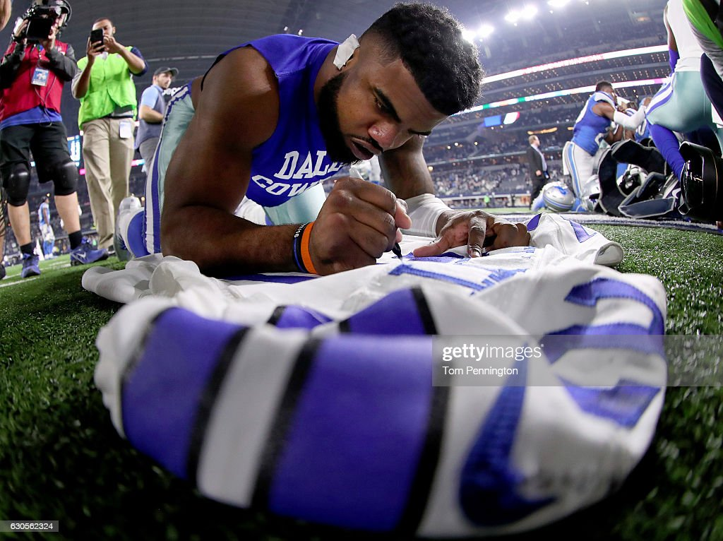 Ezekiel Elliott #21 of the Dallas Cowboys signs his jersey after the Dallas Cowboys beat the Detroit Lions 42-21 at AT&T Stadium on December 26, 2016 in Arlington, Texas.