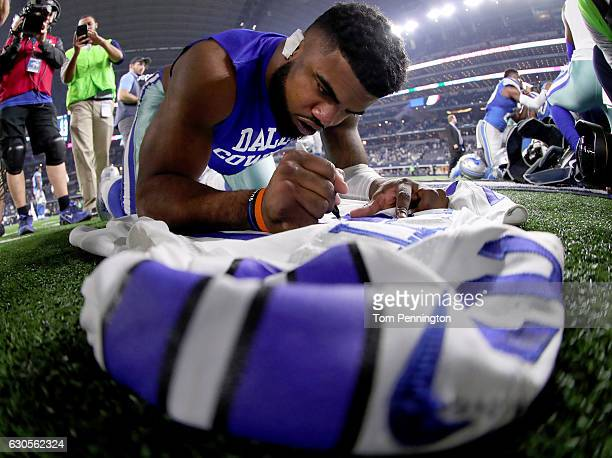 Ezekiel Elliott of the Dallas Cowboys signs his jersey after the Dallas Cowboys beat the Detroit Lions 4221 at ATT Stadium on December 26 2016 in...