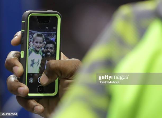 Ezekiel Elliott of the Dallas Cowboys takes a selfie with a young fan on a Iphone during a game between the Los Angeles Lakers and the Dallas...