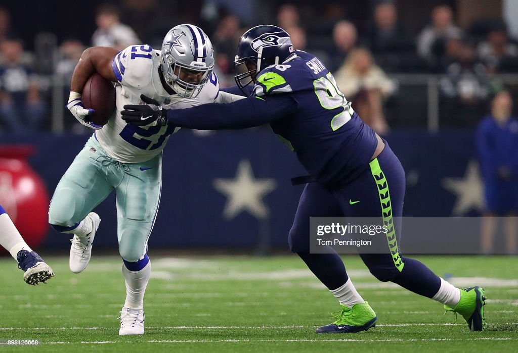 Ezekiel Elliott #21 of the Dallas Cowboys tries to evade tackle by Garrison Smith #98 of the Seattle Seahawks in the second quarter of a football game at AT&T Stadium on December 24, 2017 in Arlington, Texas.