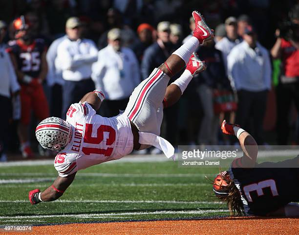 Ezekiel Elliott of the Ohio State Buckeyes is tripped up by Taylor Barton of the Illinois Fighting Illini at Memorial Stadium on November 14 2015 in...
